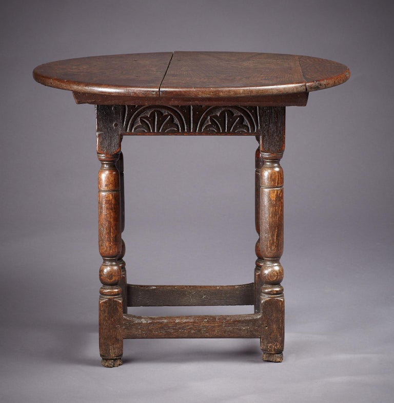 Charles I to Commonwealth period oak joined table stool, with the rare feature of original sliding circular secondary top. The stool base with rectangular top, above lunette carved frieze rails joined by bold baluster and ball turned legs, with