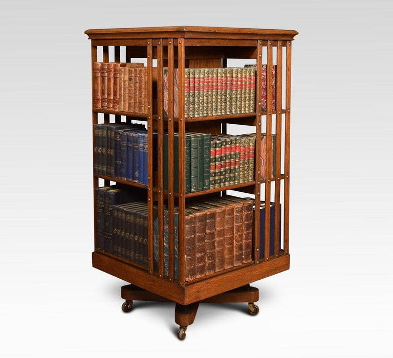 Large Edwardian oak three-tier revolving bookcase, the square moulded top above an arrangement off shelves raised up on cruciform base with metal support. Terminating in brass caps and ceramic castors. Dimensions Height 47 inches Width 23.5