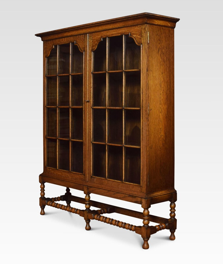 Oak bookcase the large rectangular top above two glazed beaded doors opening to reveal a shelved interior. All raised up on five barley twist supports united by stretchers.
