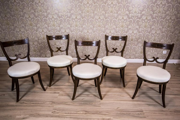 We present you this set of five chairs made of oakwood, with softly upholstered seats. The chairs are supported on legs in the Greek type. The backrests are two-tier. The upper crosspiece has a carved decoration in a frame made of stretched