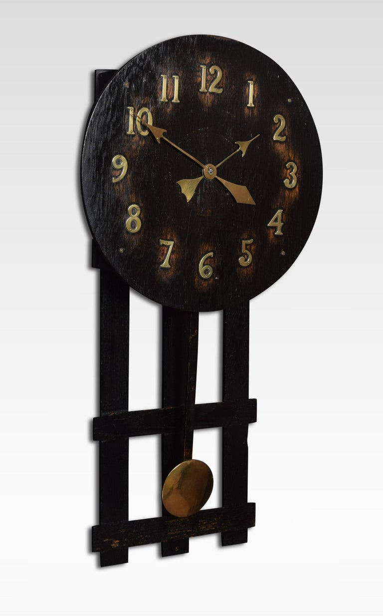 Oak missionary clock, the circular dial with Arabic numerals. To the movement striking on a gong, with stylized drop pendulum.