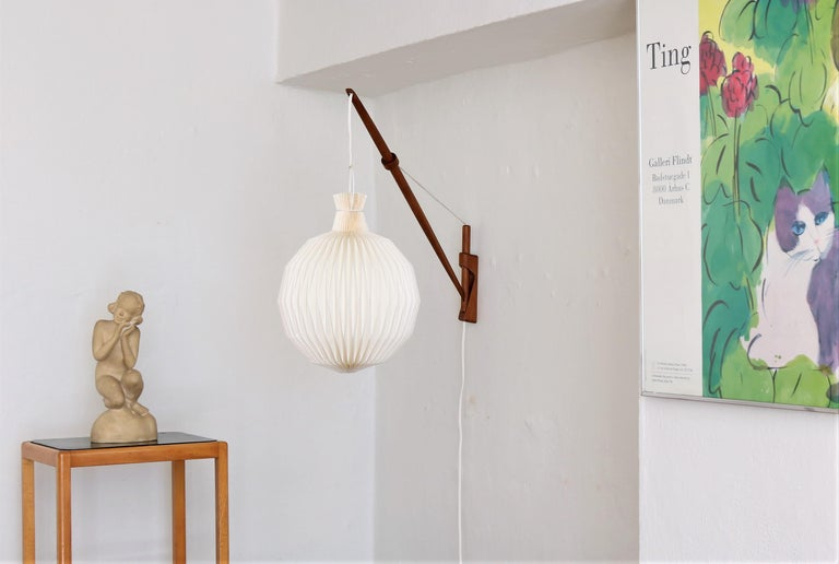 This lamp is an amazing piece of Danish modern design. The wall lamp is in patinated oak and was made in the 1950s by designers A. Bank Jensen & Kjeld Iversen for Louis Poulsen. The lamp can be adjusted in any directions and angles simply by pulling
