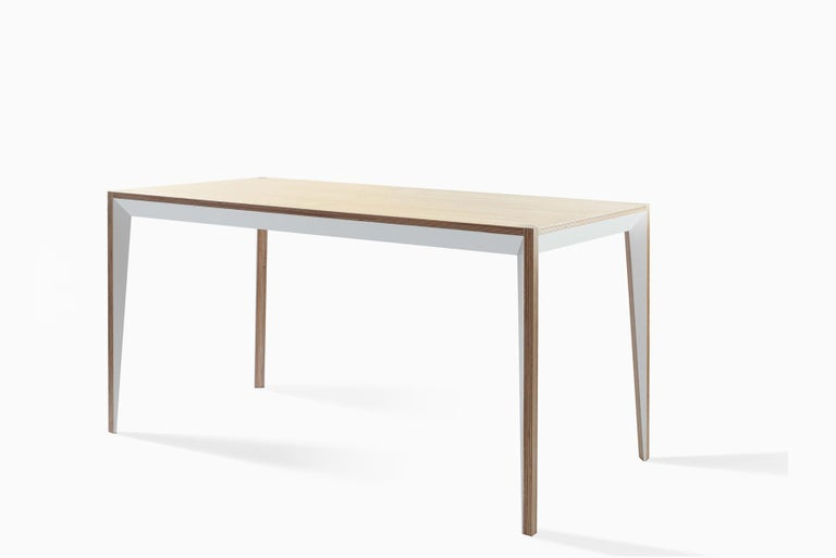 Merging clean lines with warm materials, the faceted geometry of the MiMi table creates a slender, elegant profile punctuated with painted surfaces that capture light. This modern and graceful design returns contemporary Italian craft to the office