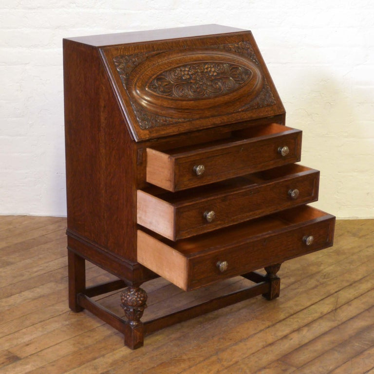 A good solid oak bureau from the 1920s but of above average quality. As you pull the fall down it draws out the fitted interior to the front edge (cantilever), the original leather writing surface is still in good order. The bureau has attractive