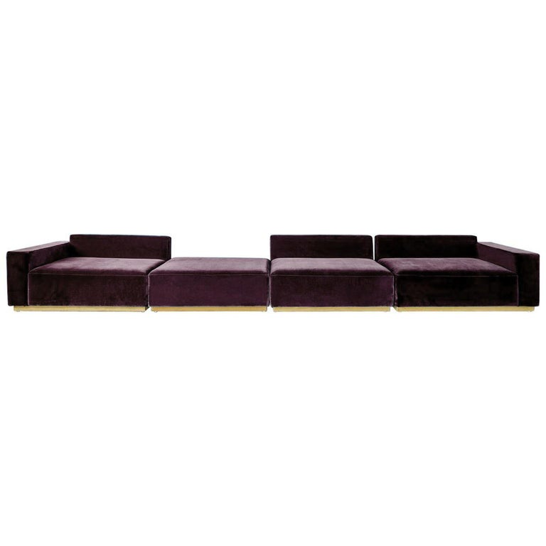 The Oberon sofa, is a contemporary sectional made of an expanse of black velvet with a yellow velvet base detailing that makes it appear to be floating above the ground.