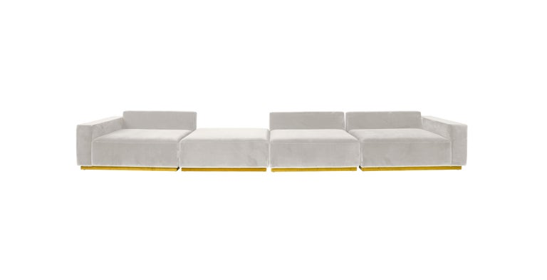 The Oberon sofa, is a contemporary sectional made of an expanse of cream velvet with a yellow velvet base detailing that makes it appear to be floating above the ground.