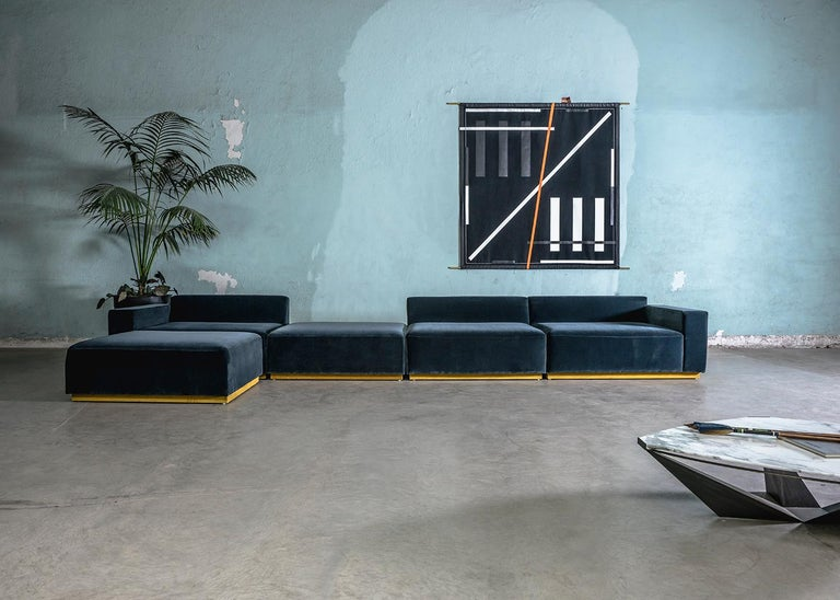 The Oberon sofa, is a contemporary sectional made of an expanse of blue velvet with a yellow velvet base detailing that makes it appear to be floating above the ground.  The aesthetic of this piece comfortably straddles the line between art and