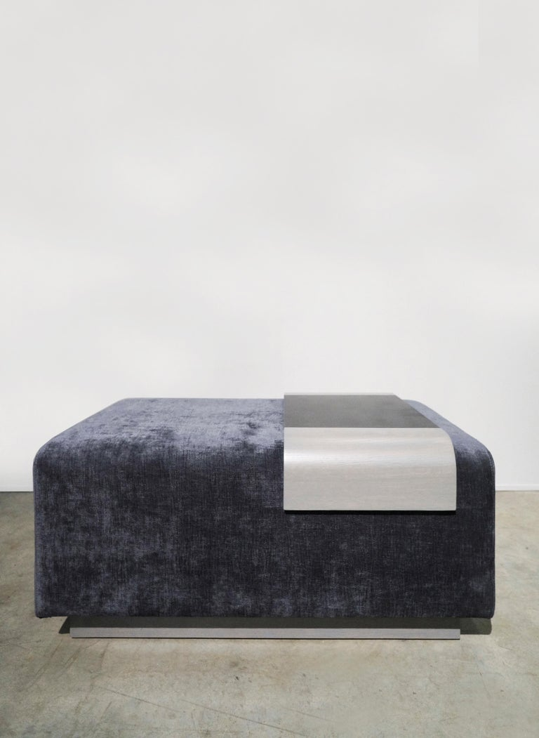 This collection is inspired by the Obi, a ribbon like accessory in Japanese traditional outfits. The seat is conformed of a rounded upholstered frame with soft edges that rest in a wooden base.   A sliding wooden and steel tray wraps around the