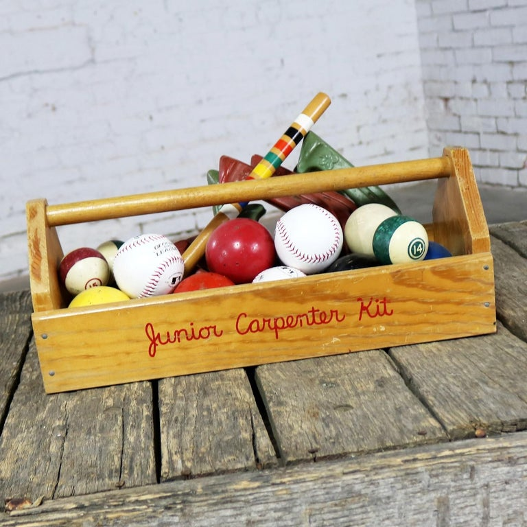 Fun and whimsical centerpiece or object d'art assemblage comprised of Junior Carpenter Kit toy tool box filled with vintage pool balls, baseballs, field hockey balls, vintage croquet balls, vintage croquet peg, and vintage rubber horseshoes. All in
