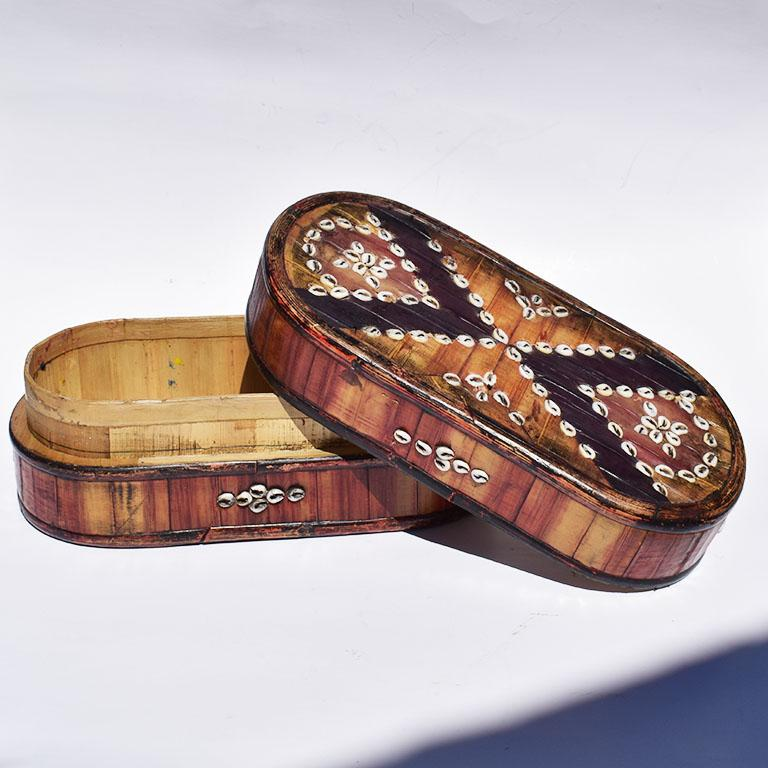 Oblong wooden box with inlaid shells. Created from bamboo or other similar material, this decorative box features white seashells in a tribal black and white design. At the top, black geometric lines are accented with white inlaid seashells. Similar