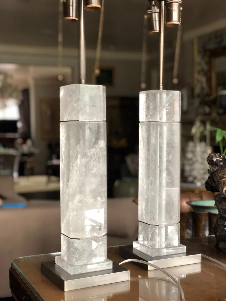 A pair of octagonal column form rock crystal quartz lamps with antique brass decoration. Created by Phoenix Gallery, NYC.  To the top of the rock crystal: 15.5