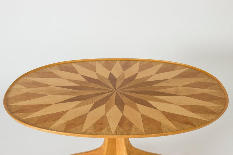 Elegant occasional table by Carl-Axel Acking, made from birch. Striking table top with inlays in an energetic, graphic design. Beautiful execution.