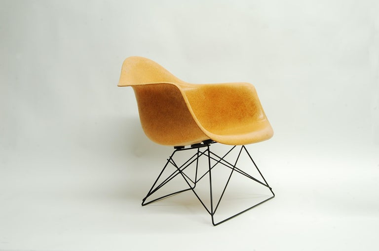 Ochre Eames armshell chair, produced by Herman Miller, circa 1960s-1970s, on black 'cats cradle' base. Armshell has great fiber content, and is Summit production (Circle