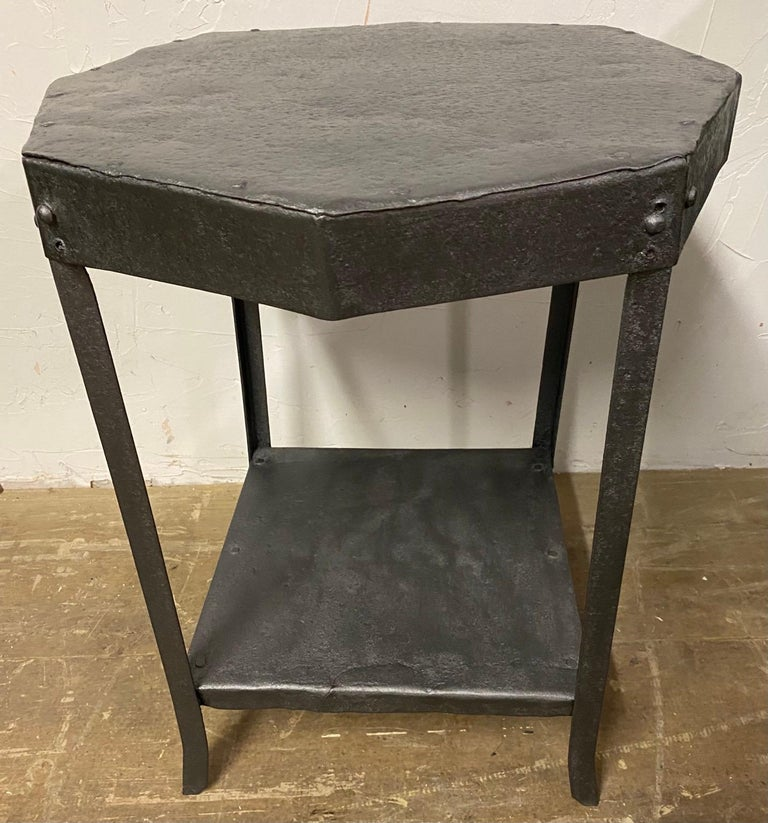 Industrial rustic French iron tables with beautiful patina on the metal. Table exhibits rustic charm and beauty. Can be used indoors as side tables or outdoors as garden table. Table has an octagon top and features shelf at the base serving to tie