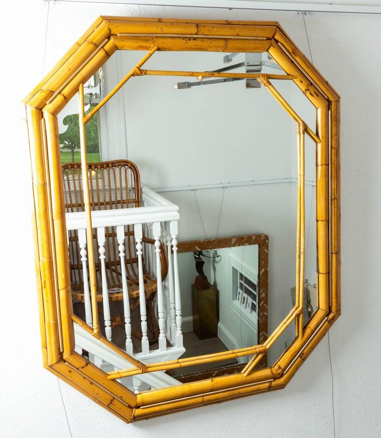 Octagonal bamboo surround mirror with brass details.