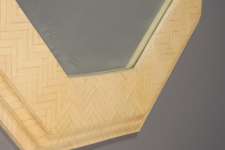 Octagonal mirror with the surface covered in a herringbone pattern in bone.