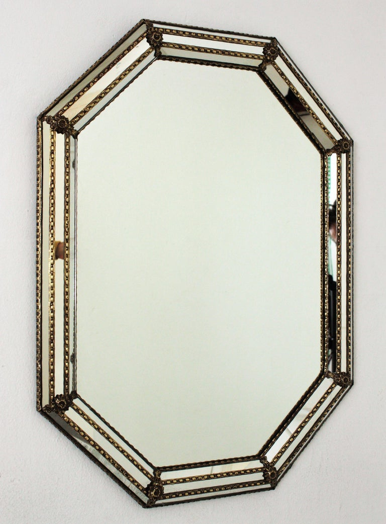 Venetian style octagonal wall mirror with gilt metal accents, Spain, 1950s This octagonal mirror has a triple mirror frame. The mirrored panels are adorned by metal patterns and flowers. This wall mirror will be perfect in a contemporary or