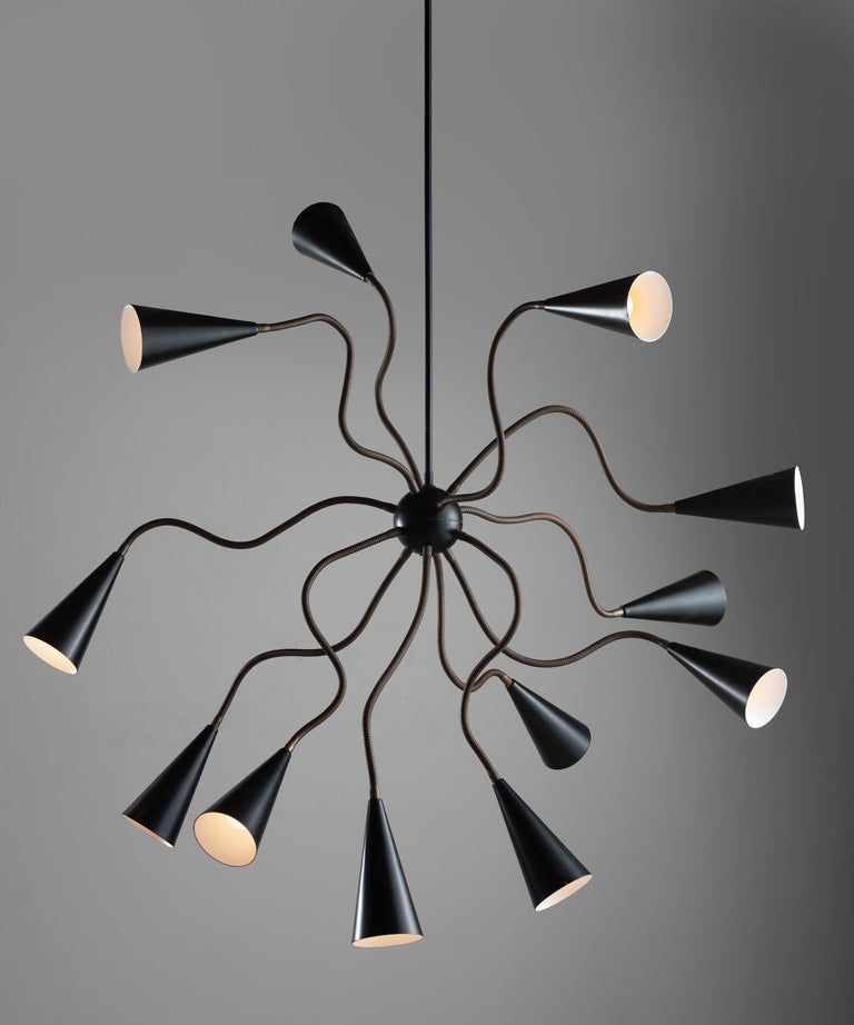 Metamorphic chandelier with 12 articulating brass arms and painted black perforated metal shades.   Measures: 63