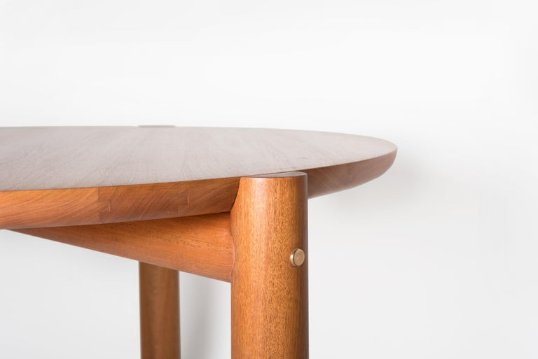 Table with a round top and three legs brought together with a clean and construction. It boasts cabinetmaking with its very beautiful and precise joints and cuts. The bronze detail, a feature on the side of each leg, fastens the base and at the same