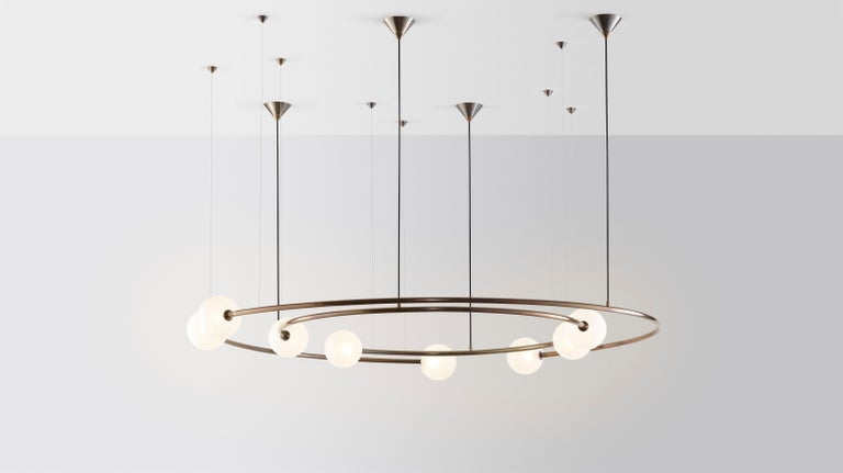 Oddments by Volker Haug  Dual ring Configuration Dimensions: W 95 D 160 H 40 cm Materials: Polished or bronzed brass Finish: Raw, satin lacquer or enamel Cord / cable: Black fabric / stainless steel Suspension: minimum 40 cm  Lamp: G9 - LED or