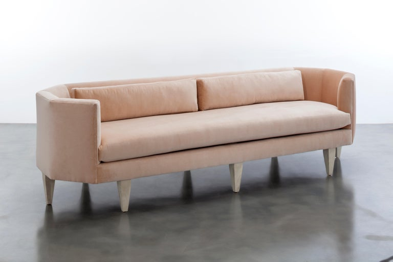 The Odette sofa features an octagonal shaped upholstered velvet seat and back with contrast lumbar pillows floating upon six wood legs. Featured in Elle Decor's
