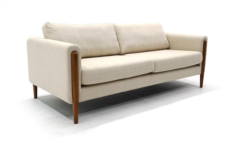 Six and a half foot off white / cream color sofa made by Neuvo. This was original purchased to stage a home for sale and is virtually unused. No signs of wear to the fabric. There may be some imperfections in the walnut upon very close inspection