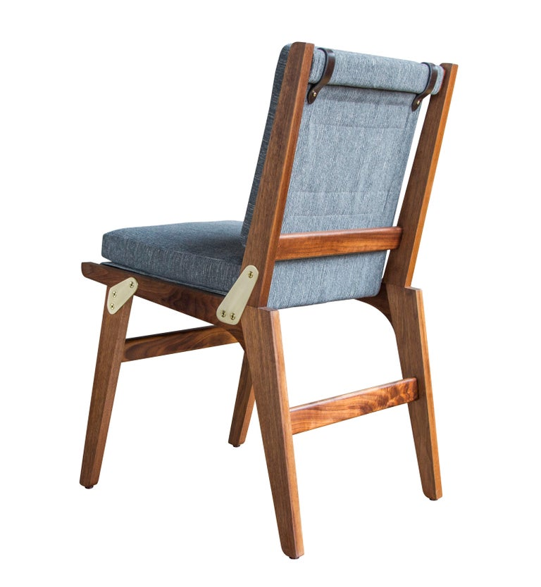 The O.F.S. dining chair is oiled walnut, lacquered satin brass and Perennials Fairhaven / Pumice upholstery with dark chocolate English bridle leather accenting straps. This chair is available in non-folding (shown) and folding versions - available