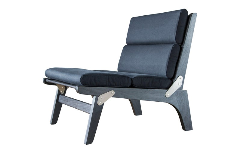 The O.F.S. lounge chair is shown in ebonized walnut, black canvas and English bridle leather strapping and stainless steel hardware. 