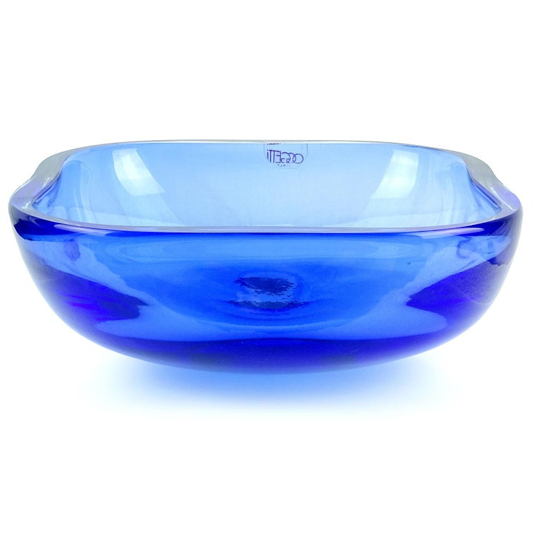 """Beautiful Murano hand blown Sommerso cobalt blue Italian art glass centerpiece bowl. Documented to the Oggetti company, with original """"Oggetti Italy"""" label still attached, circa 1970s-1980s. The piece is very large measuring 9"""" squared x 3 3/4"""