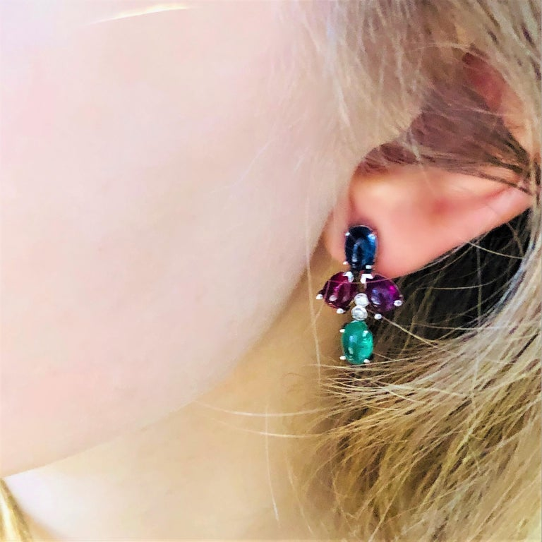 Fourteen karat white gold cluster earrings  With diamond and cabochon emerald, sapphire and ruby Earrings  one inch long Two cabochon emerald weighing 2.00 carat Four pear-shaped cabochon ruby weighing 4.35 carat Two cabochon sapphire weighing 2.75