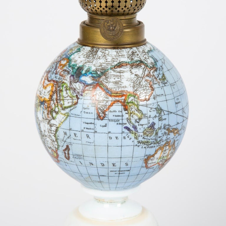 A rare late 19th century oil lamp with a globe shade and base decorated with a castle set in a rural scene, circa 1885.  Northern European for the French market. The countries and seas indicated on the globe written in French.   Burner made by