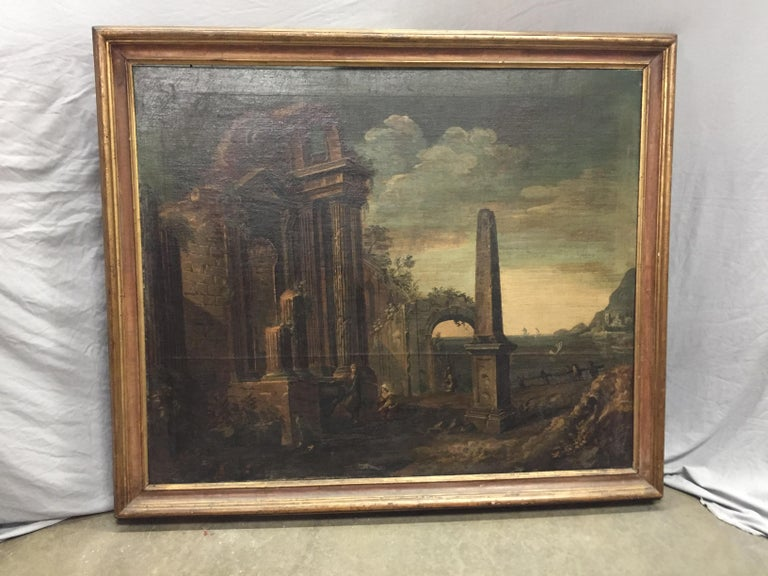 Oil on canvas of Roman ruins and a large obelisk on a lush landscape with various Classical figures. A mountain landscape off to the distance with a sunset sky.  Late 17th-early 18th century. In gilt frame.   Meticulous attention was used to