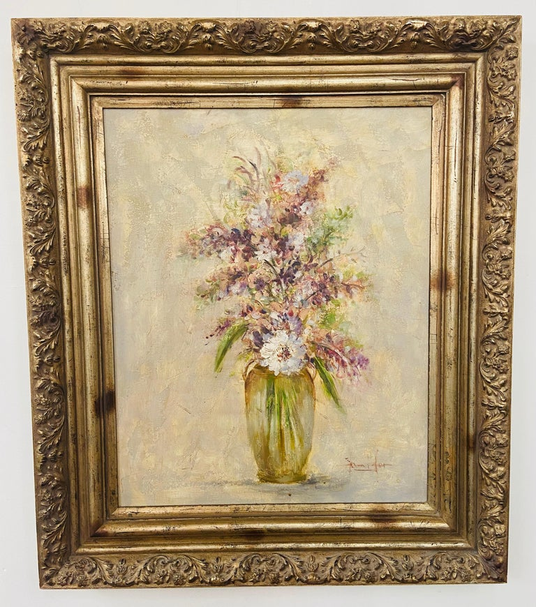 A gorgeous oil on canvas painting in a pastel tone depicting a vase with white flowers and lavenders in a vase. The painting is beautifully framed in a custom gilt carved wood frame and is signed by artist Jennifer.   Dimensions: 40.5