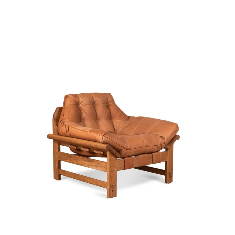 The Ojai lounge chair features a solid white oak or solid walnut base and a single tufted leather cushion with leather straps. Shown here in deer tan leather and oiled oak.