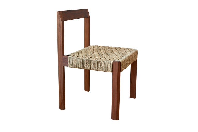 The faceted armless dining chair made in the USA with handwoven Danish cord seat by Casey McCafferty.  Shown in oiled walnut.  Available finishes: Oiled black walnut, oiled white oak, bleached white oak, charred ash, oxidized maple  COM