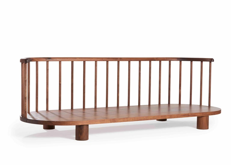 Bone sofa with brass suture detail and spindle back. Made in the USA by Casey McCafferty.  Shown in oiled walnut.  The Bone collection was inspired by the concept of exposure: revealing the structure or