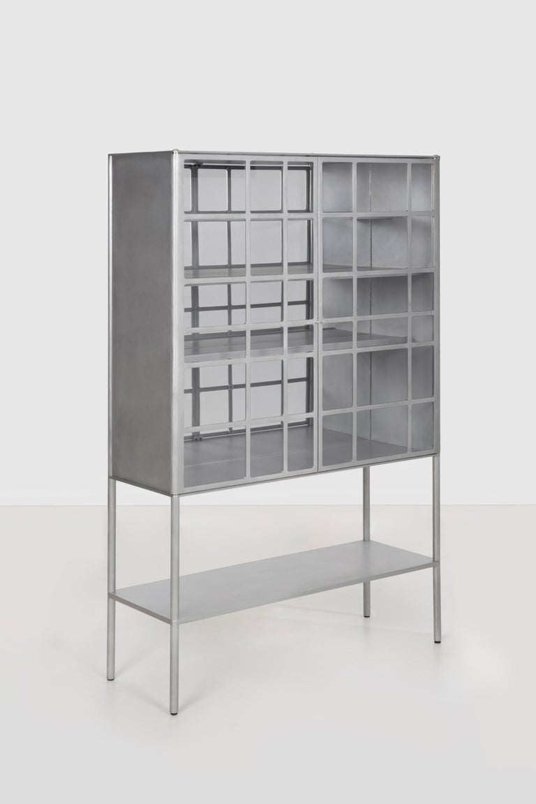 OK whiskey cabinet, in cut, milled, and machined aluminum. Milled acrylic window inserts are set from the reverse and fastened with a custom washer. Inset foot levelers are concealed within the solid aluminum leg. The lower shelf is a solid