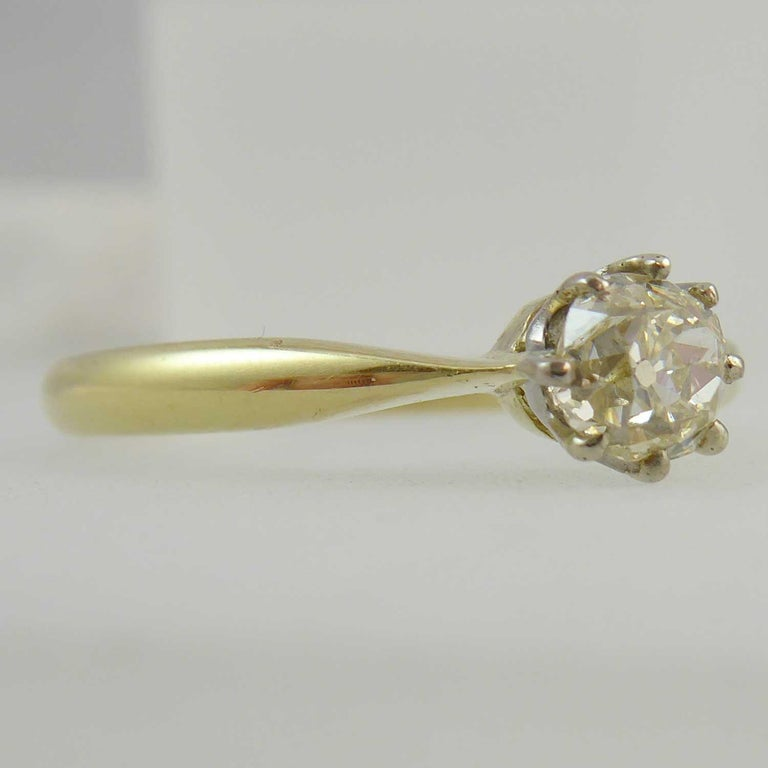 A delightful vintage solitaire ring perfect for the petite hand.  Set with an old brilliant cut diamond in a white claw setting and with a known weight of 0.65ct.  Clarity is assessed as VS and colour tinted.  Plain polished yellow band stamped 18ct