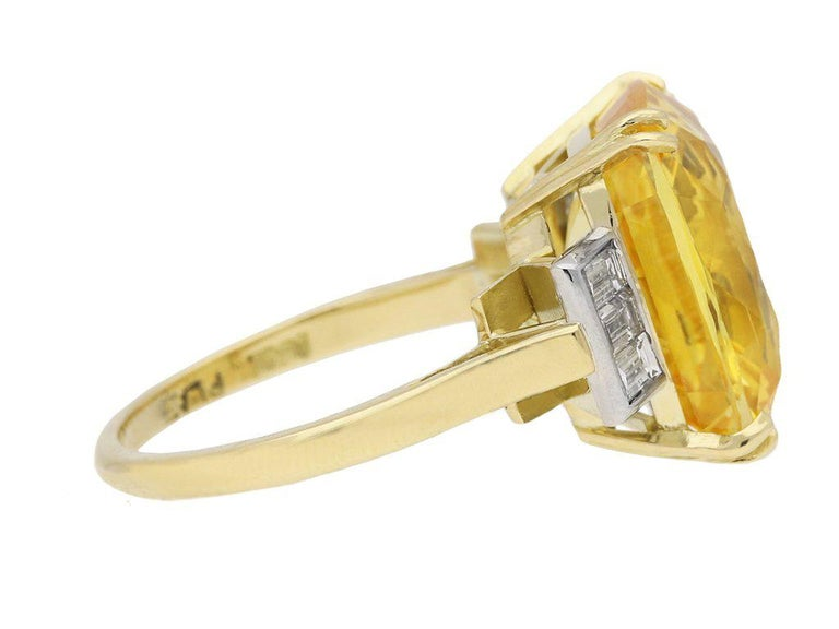 Yellow sapphire and diamond ring. Set with a cushion shape old cut natural unenhanced Ceylon sapphire in an open back four split claw setting with an approximate weight of 12.23 carats, flanked by six rectangular baguette cut diamonds in open back
