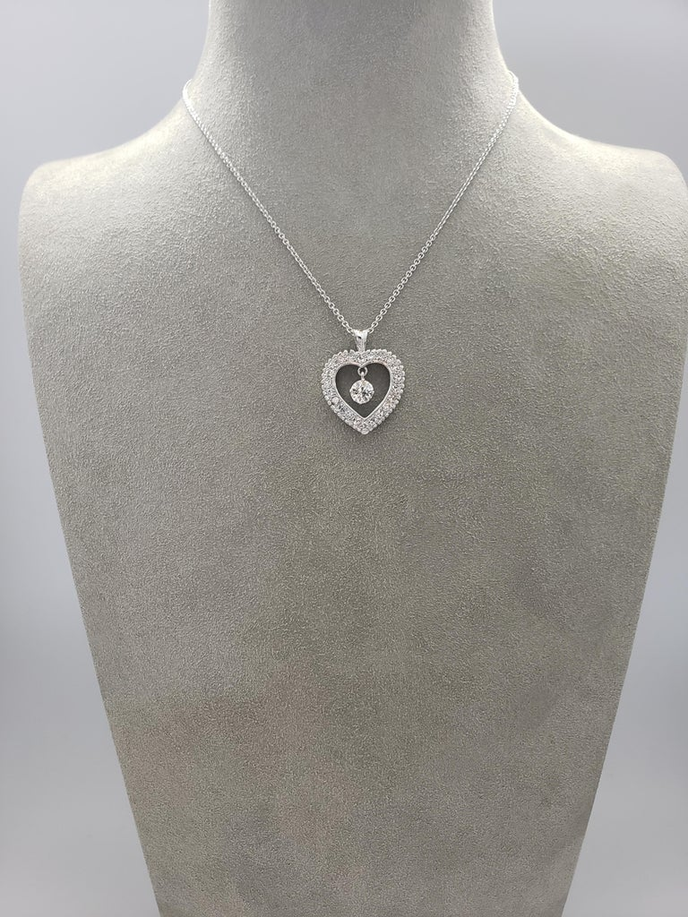 A pendant necklace of open-work design, showcases a single old european cut diamond weighing 0.72 carats, surrounded by french cut round diamonds set in a heart shape mounting. Accent diamonds weigh 1.09 carats total.