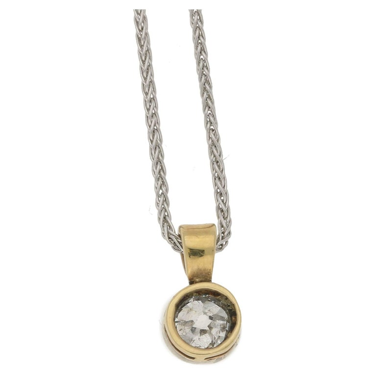 A hand cut Old European cut diamond single stone pendant collet set in millé-grained platinum on 18ct yellow gold. Assessed diamond colour: G/H. Assessed diamond clarity: I2. Hung on a fixed wedge shaped bale on a 20 inch, white gold spiga style
