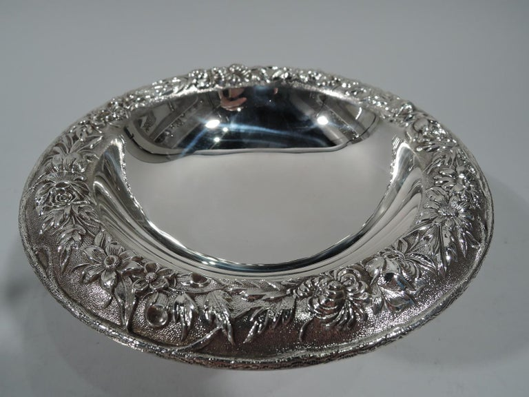Old fashioned sterling silver compote. Made by S. Kirk & Son in Baltimore. Deep round bowl with curved rim, spool support, and stepped round foot. Rim has repousse floral garland on stippled ground. Hallmark (1932-61). Number 436. Weight: 6.4 troy
