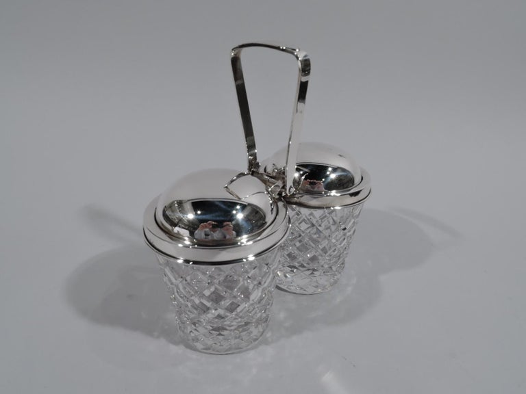 Old-fashioned sterling silver and glass double jam jars. Retailed by Cartier in New York, circa 1950. Two jars each with straight and tapering sides and raised diaper pattern. Sterling silver collars joined by mount with tapering swing handle. Domed