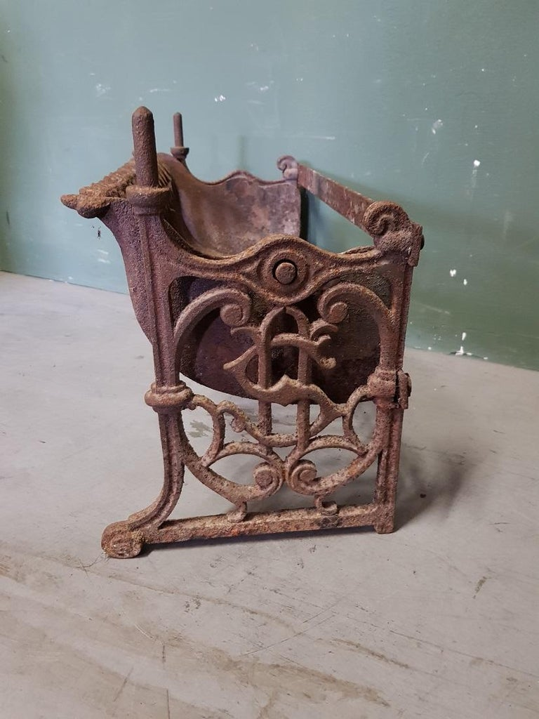 Old French cast iron rotating fireplace grate with neo-Gothic elements and the sides with a Dollar-like sign, this is in a good but used condition. Originating from the 1st half of the 20th century.