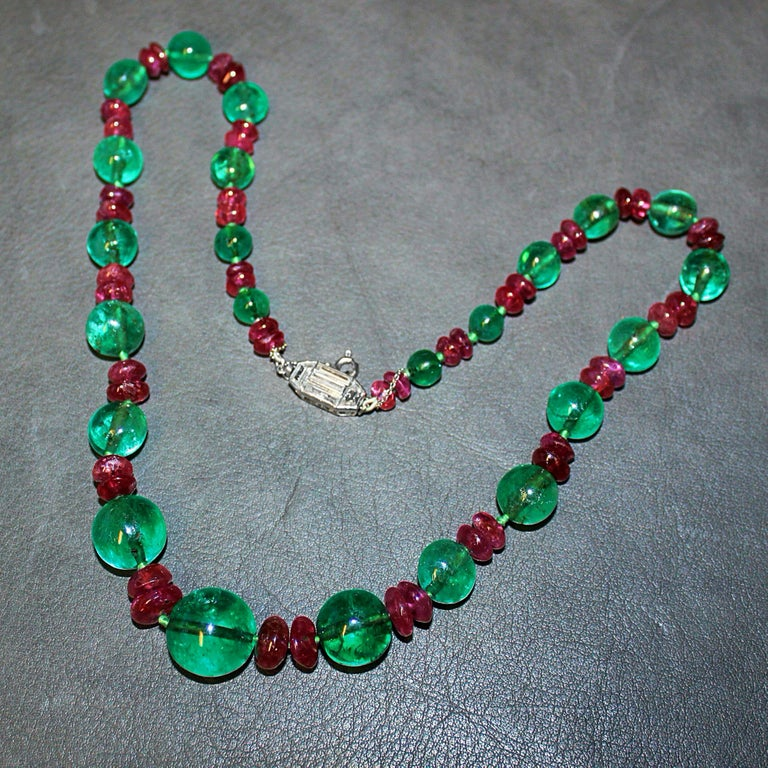 A magnificent French emerald, ruby and diamond Art Deco necklace, ca. 1920s.   The large old-mine emerald beads have a deep green colour and crystal. They are alternatingly strung next to two old ruby beads in a graduating manner. The clasp at the