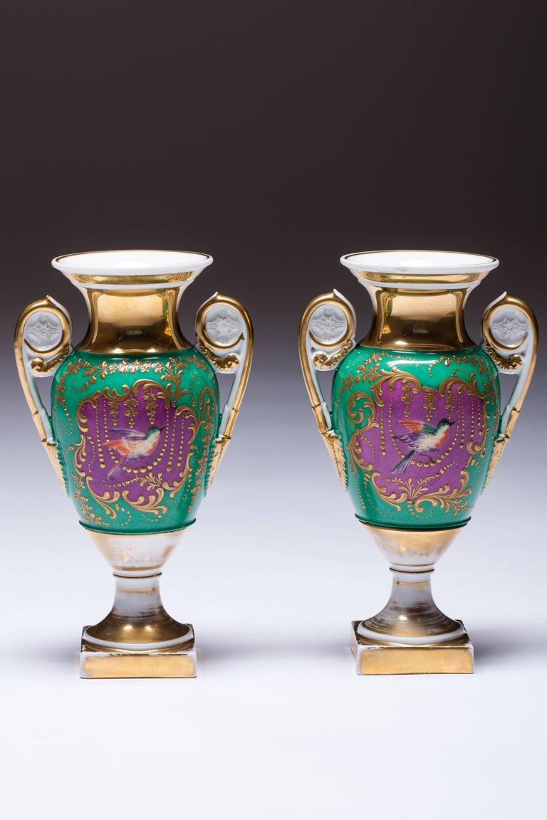 Especially rare vases decorated with hand-painted bird pink background. A beaded ornament around it, for which the green background is framed. The vases are dipped in porcelain biscuit and gold in the same way as the whole vase.