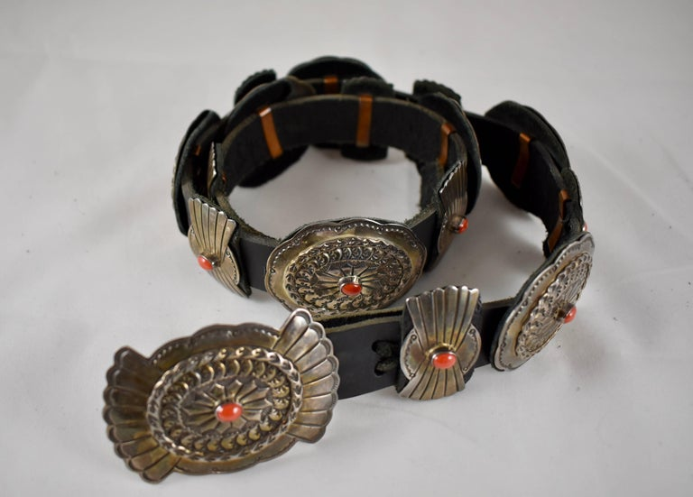 A vintage, Old Pawn Navajo Concho Belt, marked Sterling and LC, attributed to Lucille Calladitto. 16 heavy stamped sterling silver Conchos are set with cabochon cut ox-blood coral stones, held in place on a black leather belt measuring 38 in.