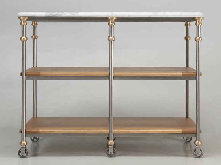 Handcrafted in Chicago, from stainless steel, solid bronze and wire-brushed, rift-cut white oak shelves, with a Carrera marble-top (butcher block available as an upgrade). Closely working with designer firms worldwide, this fine Industrial style
