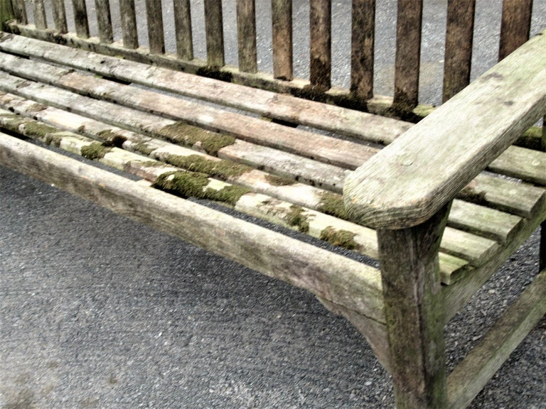 Teak wood slat back long garden bench with pegged construction in overall beautiful naturally weathered driftwood gray surface with algae lichen growth from years of outside use. Circa 1940 - 1960