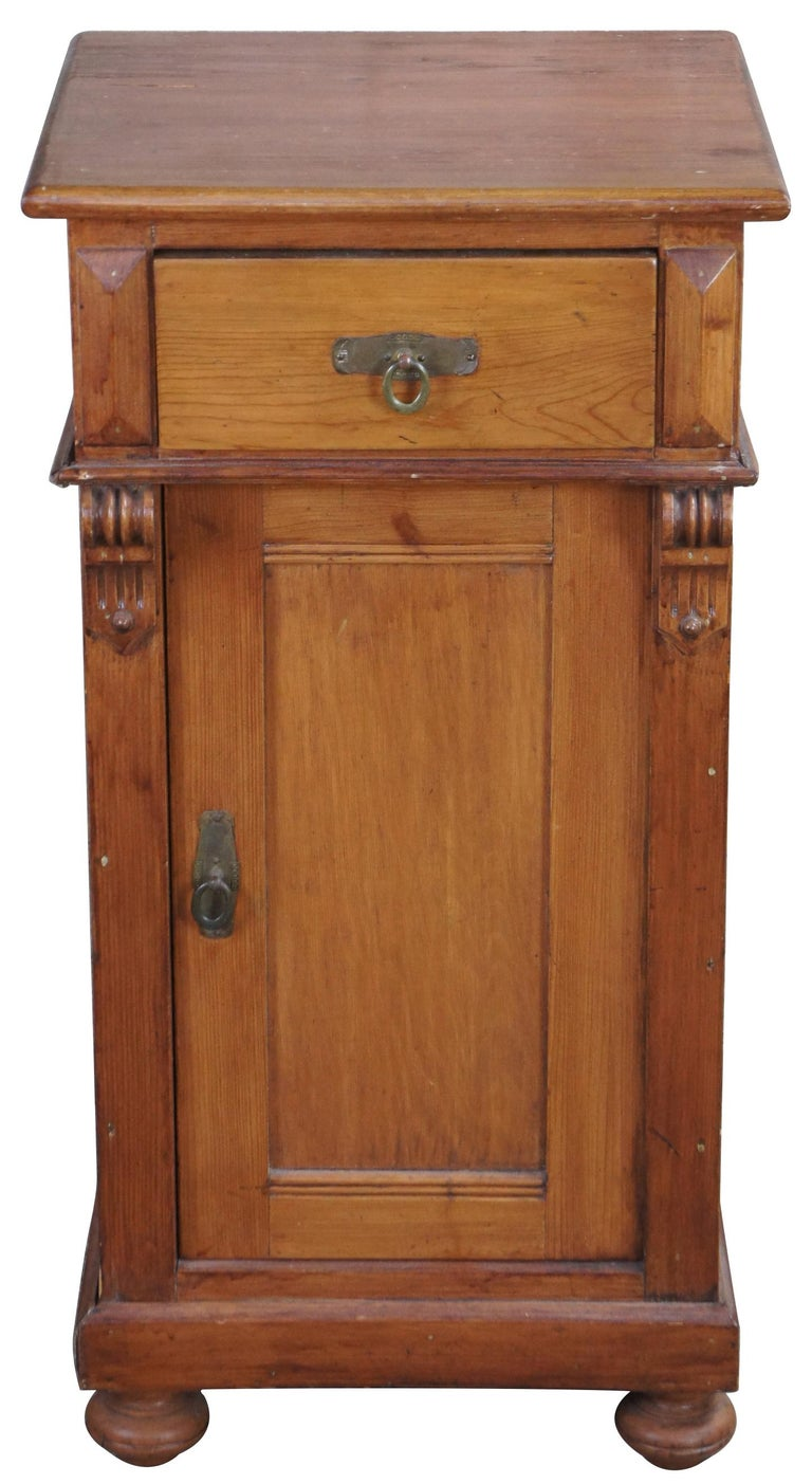 Late 20th century English pine cabinet. Features a square shaped case with upper dovetailed drawer, lower cabinet, scrolled corbels and bun feet. Measure: 32
